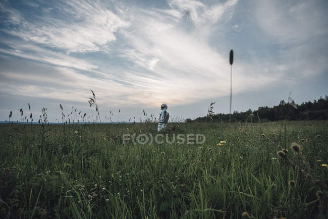 Spaceman exploring nature, standing in blooming meadow — Stock Photo