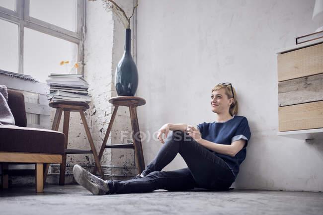 Усміхнена жінка сидить на підлозі в лофт і мріє — стокове фото