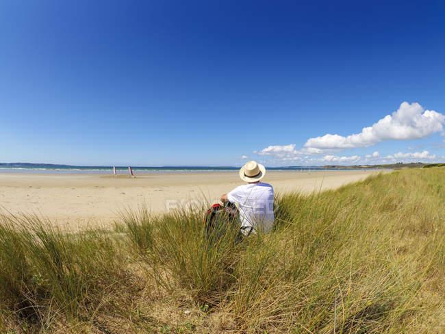 Франция, Бретань, Старший, отдыхающий на пляже, сидящий на дюне — стоковое фото
