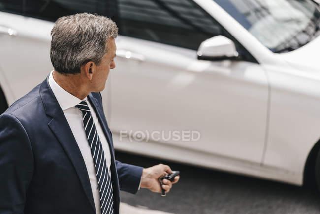 Homme d'affaires utilisant la clef de commande à distance de la voiture — Photo de stock