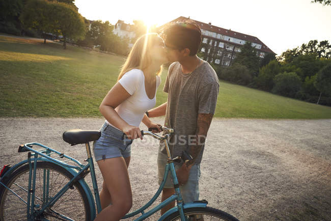 Young woman with bicycle, kissing her boyfriend in park, sunset shine on background — Stock Photo
