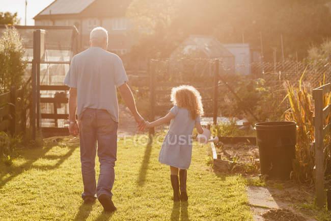 Bambina mano nella mano con lo zio in giardino — Foto stock