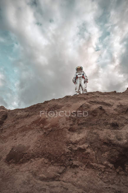 Spaceman standing on slope of nameless planet — Stock Photo