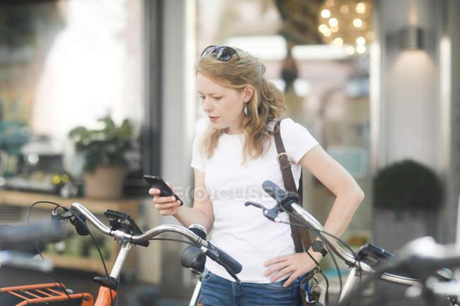 Германия, молодая женщина со смартфоном арендующая городской велосипед — стоковое фото