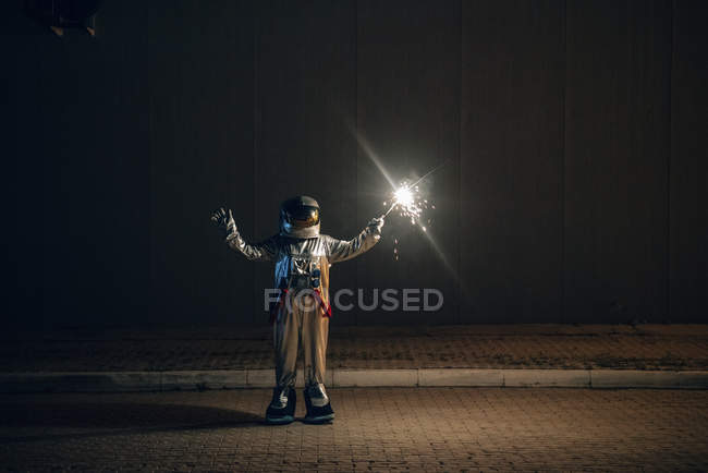 Spaceman standing on road at night holding sparkler — Stock Photo