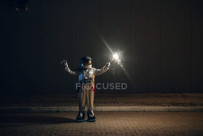 Raumfahrer steht nachts mit Wunderkerze auf der Straße — Stockfoto