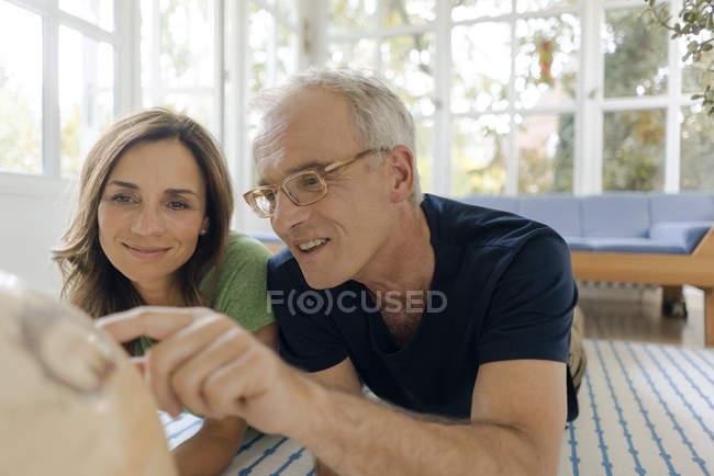 Зрелая пара лежит на полу дома и смотрит на глобус — стоковое фото