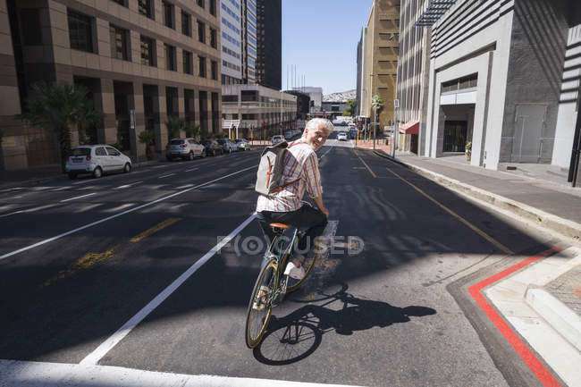 Smiling mature man riding bicycle in city and looking over shoulder — Stock Photo
