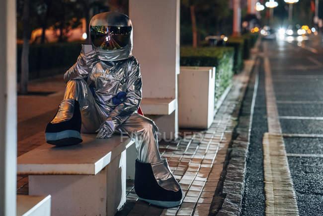 Spaceman sentado en el banco en la parada de autobús por la noche y sosteniendo el teléfono celular - foto de stock