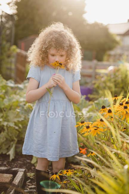 Menina cheirando flores no jardim — Fotografia de Stock