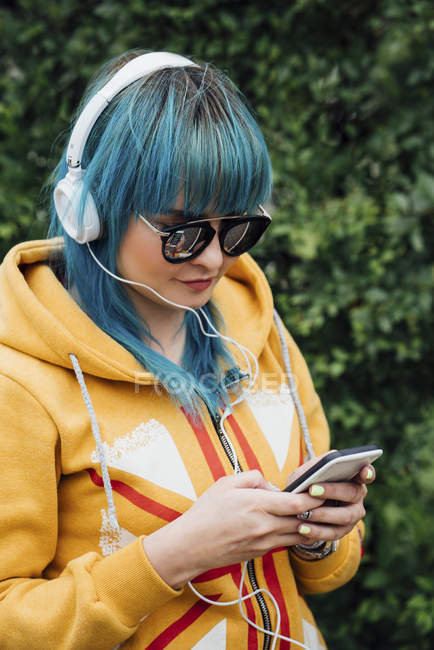 Portrait of young woman with dyed blue hair listening music with headphones looking at smartphone — Stock Photo