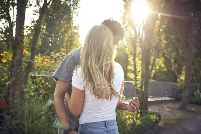 Feliz pareja joven abrazando y besándose en un parque en verano - foto de stock