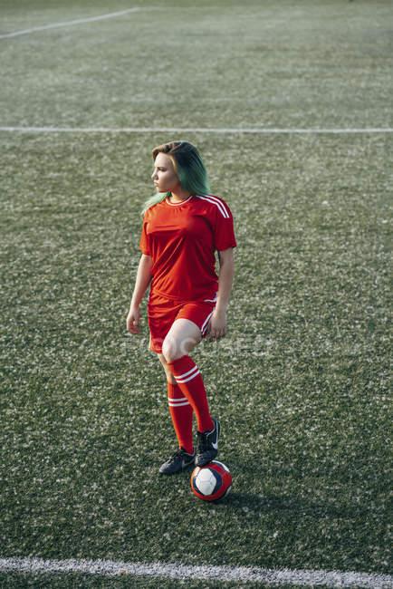 Молода жінка, що стоїть на футбольному грунті з м'ячем — стокове фото