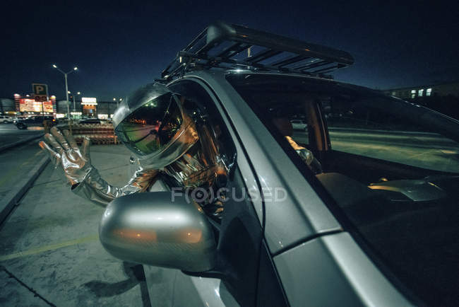 Spaceman waving out of car at night in city — Stock Photo