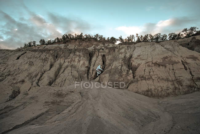 Spaceman climbing cliff on nameless planet — Stock Photo