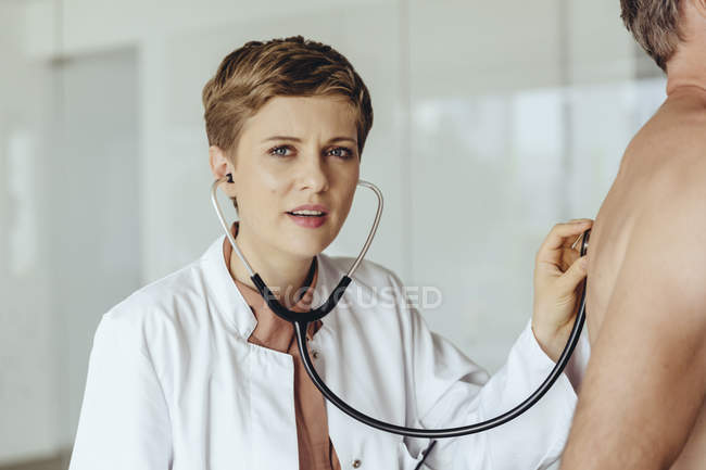 Female doctor examining patient with a stethoscope - foto de stock
