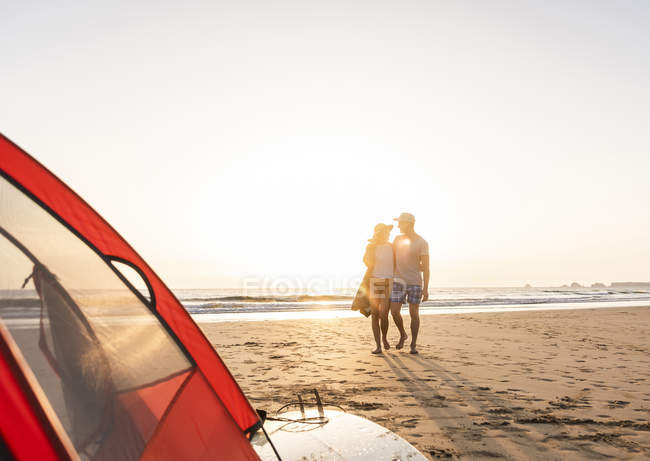 Coppia romantica campeggio sulla spiaggia, facendo passeggiata in spiaggia al tramonto — Foto stock