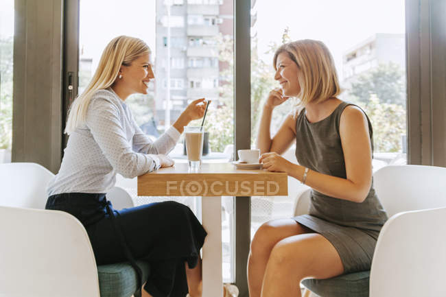 Two young women meeting in a cafe — Stock Photo