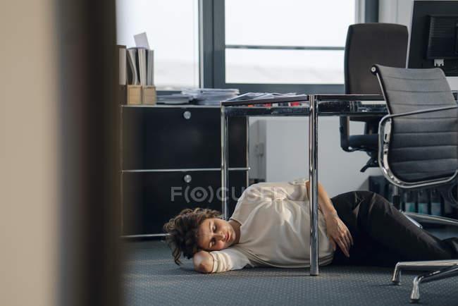 Mulher de negócios tired que dorme no escritório no assoalho — Fotografia de Stock