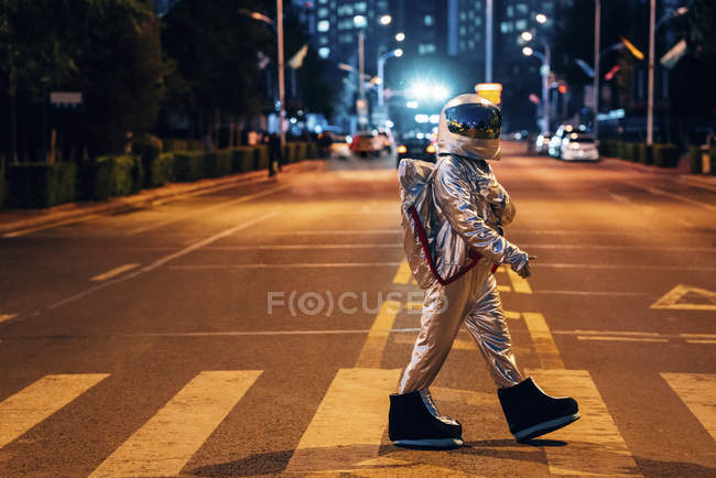 Spaceman walking on a street in city at night — Stock Photo