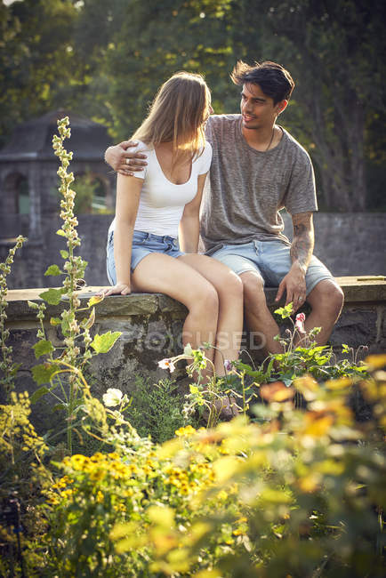 Romantic young couple sitting on wall in a park, with arms around — Stock Photo