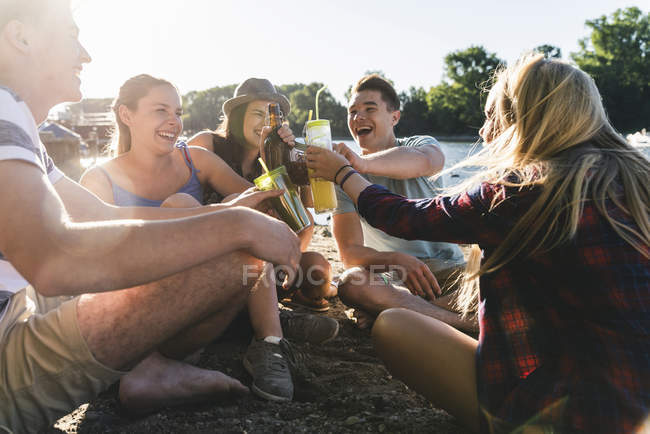Group of happy friends sitting at riverside and toasting with drinks — Stock Photo