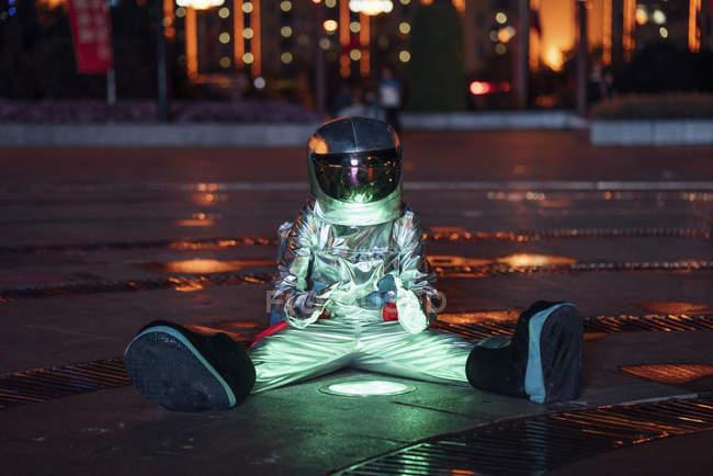 Spaceman sentado en la lámpara en la plaza de la ciudad por la noche y las manos de calentamiento - foto de stock