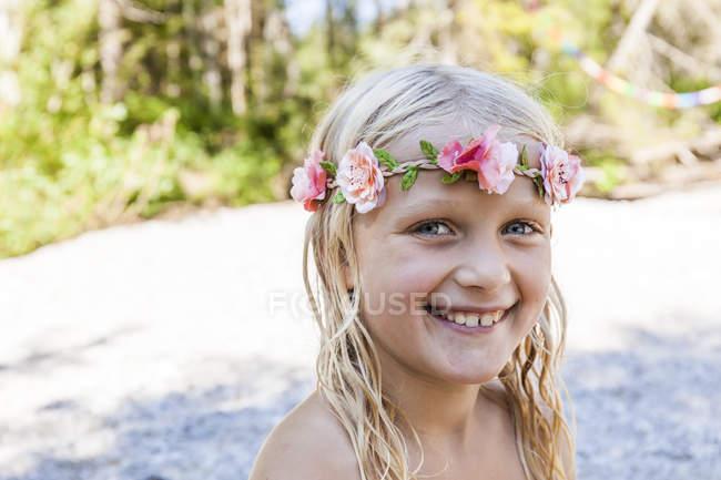 Портрет счастливой девушки в цветочной короне на улице летом — стоковое фото