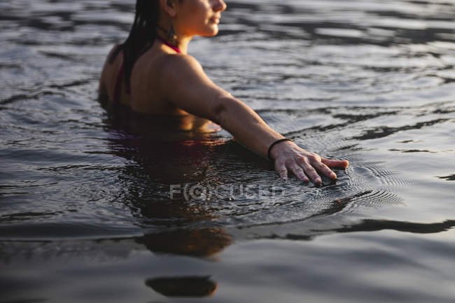 Young woman touching the water surface in a lake — Stock Photo