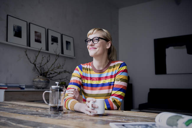 Portrait of smiling woman with cup of coffee sitting in loft — Stock Photo