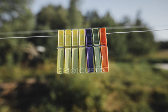 Row of clothes pegs hanging side by side on washing line — Stock Photo