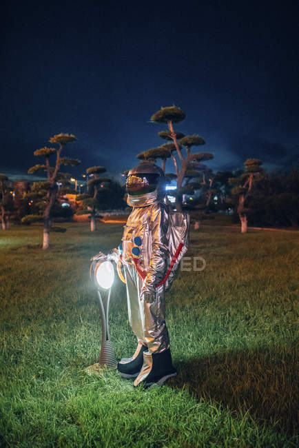 Spaceman standing at lamp in a park at night — Stock Photo