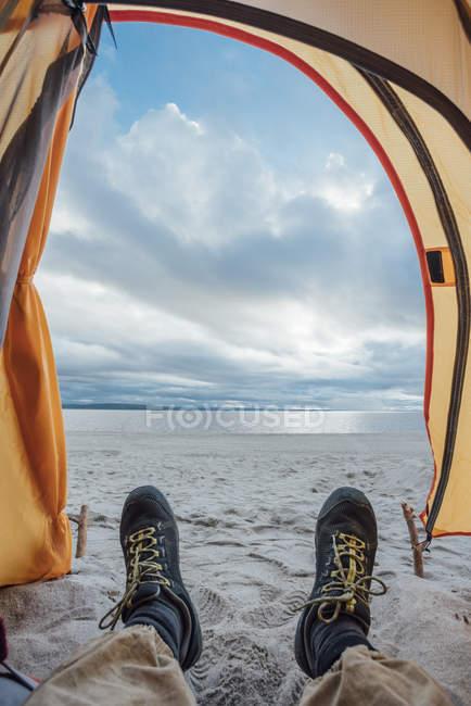 Pieds de l'homme, couché dans la tente sur la plage — Photo de stock