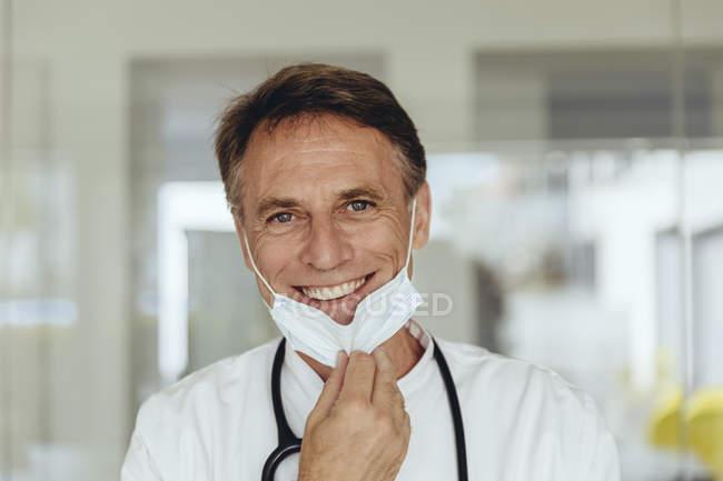Retrato de un médico, quitándose la máscara quirúrgica, sonriendo - foto de stock