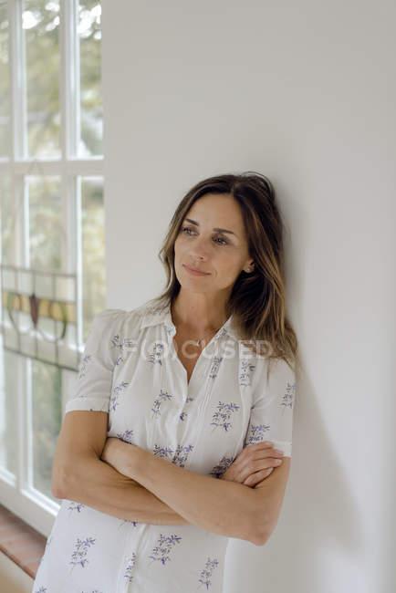 Mujer madura pensativa en casa apoyada contra una pared - foto de stock