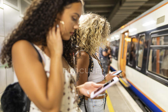 Young women with cell phones waiting at underground station platform — Stock Photo