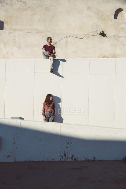 Mann und Frau stehen und sitzen auf verschiedenen Ebenen einer Wand — Stockfoto