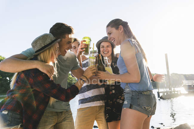 Group of happy friends standing at  riverside and toasting with drinks — Stock Photo