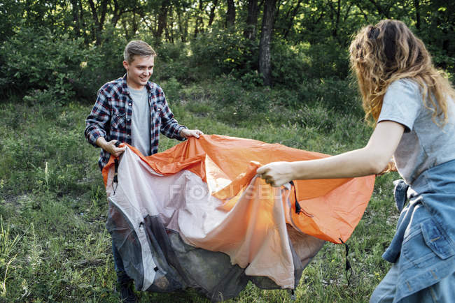Young couple setting up tent in nature — стокове фото