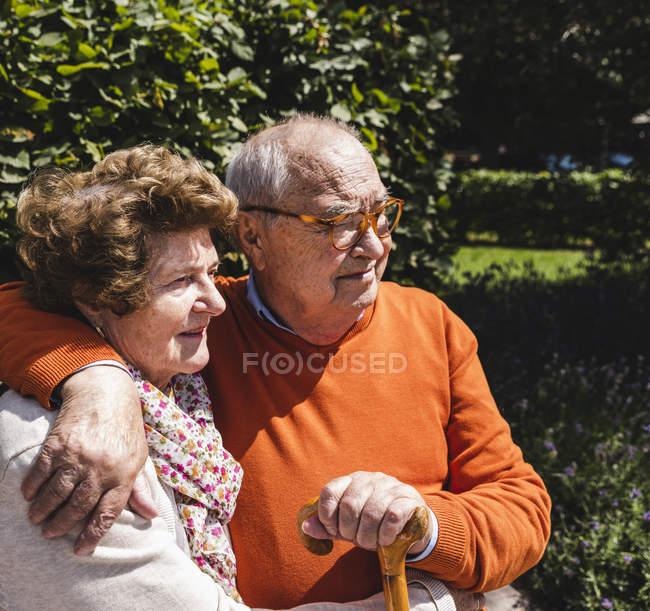 Seniorenpaar sitzt mit Armen auf Bank im Park — Stockfoto