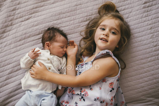 Smiling girl lying on blanket, cuddling with her baby brother — Stock Photo