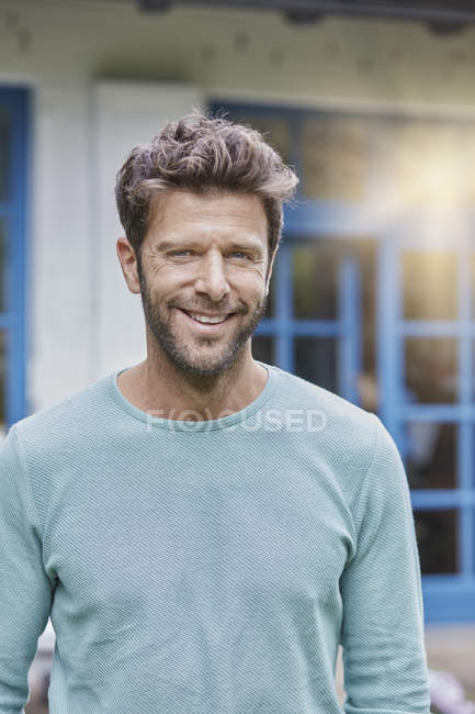 Portrait of smiling man in front of house with blue window — Stock Photo