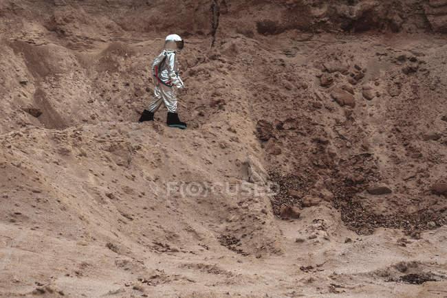 Spaceman que explora o planeta sem nome ao andar no deserto — Fotografia de Stock