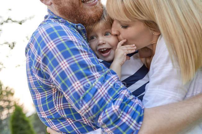 Des parents heureux embrassant sa fille à l'extérieur — Photo de stock