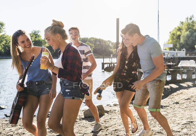Group of happy friends walking at the riverside — Stock Photo