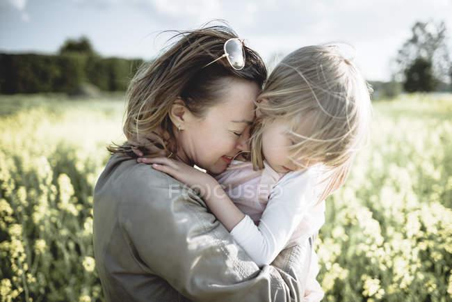 Mère et petite fille ensemble dans un champ de viol — Photo de stock