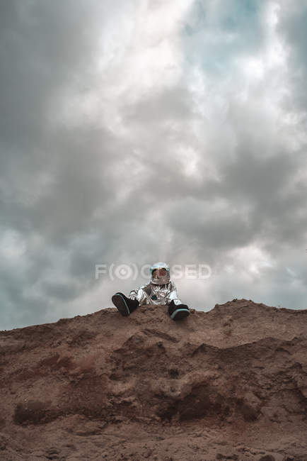 Spaceman sitting on cliff of nameless planet — Stock Photo