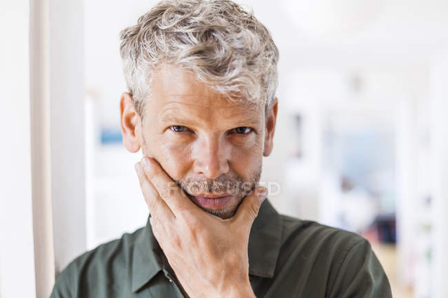 Portrait of mature man with grey hair and stubble at home — Stock Photo
