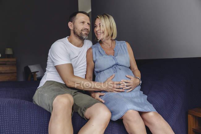 Hombre maduro y esposa madura embarazada sentada en la cama y tocando el vientre - foto de stock