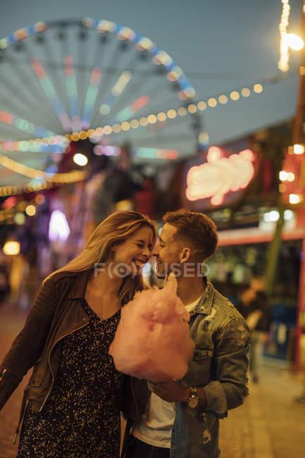 Casal romântico em uma feira de diversão comendo Candyfloss — Fotografia de Stock